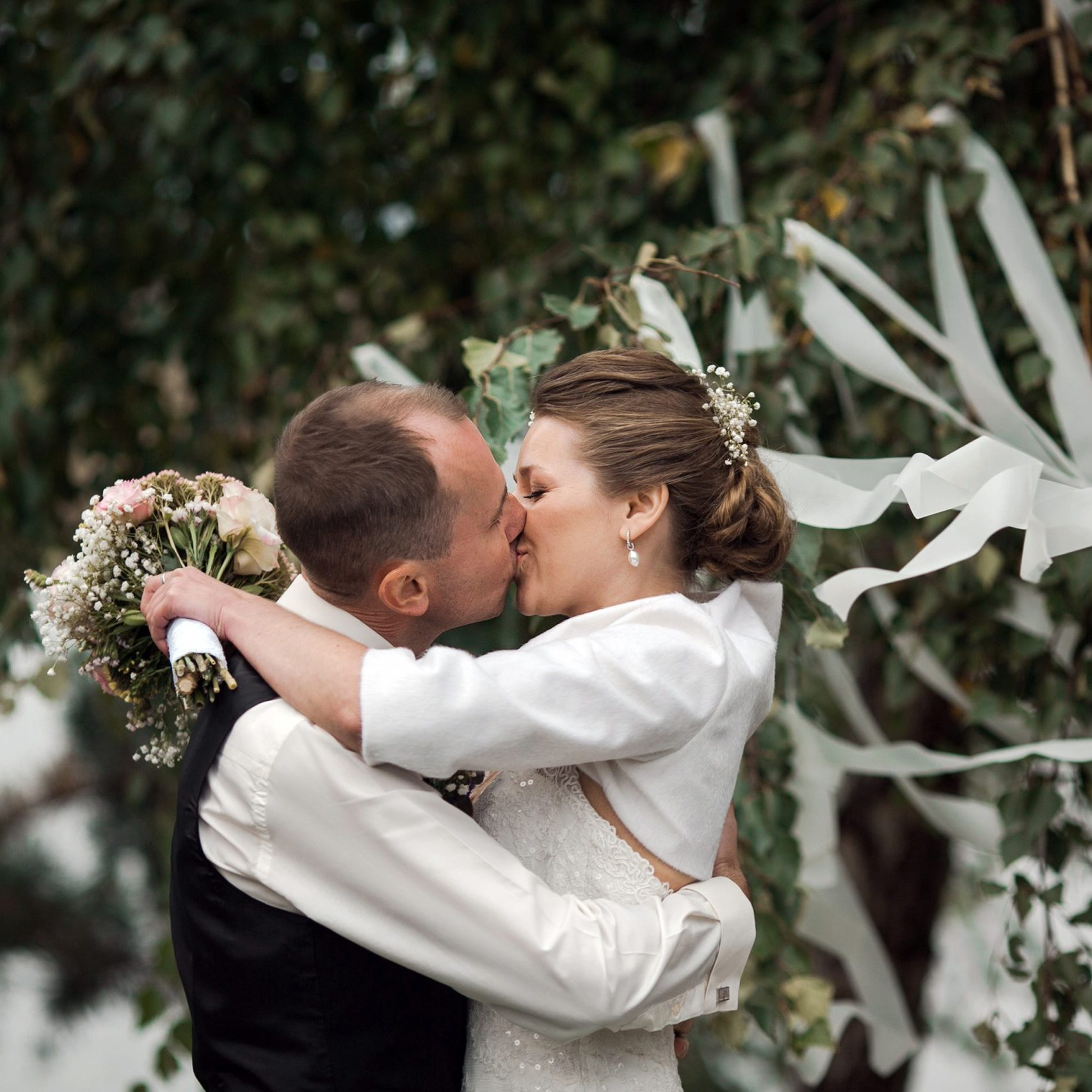 beautiful bride kisses the groom at a wedding ceremony